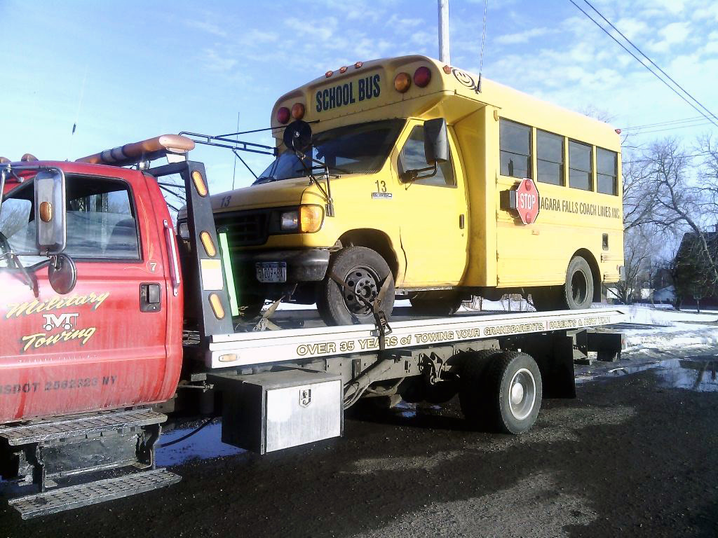 Military Towing LLC tow truck carrying school bus in Niagara Falls